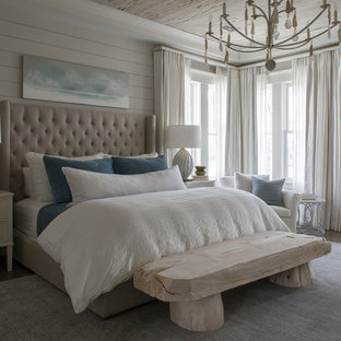 Photo of a beach style bedroom in Miami with beige walls, dark hardwood floors and brown floor.