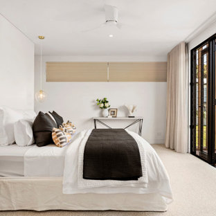 Large beach style master bedroom in Sydney with white walls, carpet and beige floor.