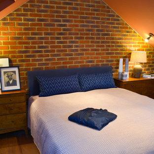Modelo de dormitorio tipo loft, clásico, de tamaño medio, con parades naranjas y suelo de madera en tonos medios