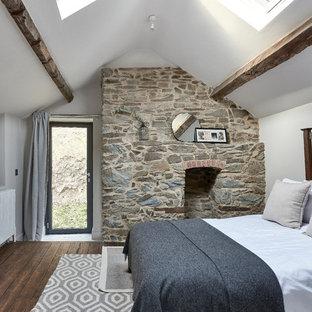 Esempio di una camera degli ospiti scandinava di medie dimensioni con pareti bianche, parquet scuro, camino classico, cornice del camino in pietra, pavimento marrone e travi a vista
