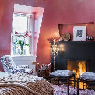 Aménagement d'une grande chambre parentale campagne avec un mur rouge, un sol en bois foncé, une cheminée standard et un manteau de cheminée en métal.