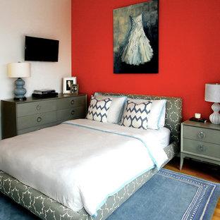 Foto på ett litet funkis gästrum, med orange väggar och mellanmörkt trägolv