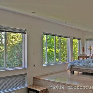 Foto de dormitorio tipo loft, contemporáneo, pequeño, sin chimenea, con suelo de bambú y paredes blancas