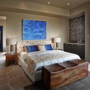 Imagen de dormitorio principal, de estilo americano, grande, con paredes beige, suelo de piedra caliza y suelo marrón