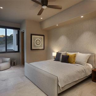 Diseño de habitación de invitados de estilo americano, grande, con paredes beige, suelo de baldosas de porcelana, marco de chimenea de hormigón y suelo gris