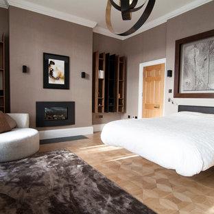 ロンドンの中サイズのコンテンポラリースタイルのおしゃれな主寝室 (無垢フローリング、標準型暖炉、金属の暖炉まわり、グレーの壁) のインテリア