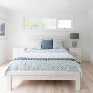 Foto de dormitorio principal, costero, de tamaño medio, sin chimenea, con paredes blancas, suelo laminado y suelo amarillo
