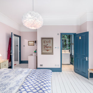 Vintage guest bedroom in London with pink walls, painted wood flooring and white floors.
