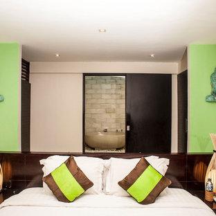 Esempio di una camera degli ospiti etnica di medie dimensioni con pareti verdi, pavimento in cemento e pavimento beige