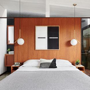 Foto di una piccola camera matrimoniale design con pareti marroni, pavimento in cemento e pavimento grigio
