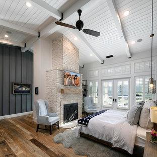 Foto de dormitorio principal, campestre, grande, con paredes blancas, suelo de madera en tonos medios, chimenea tradicional, marco de chimenea de ladrillo y suelo marrón