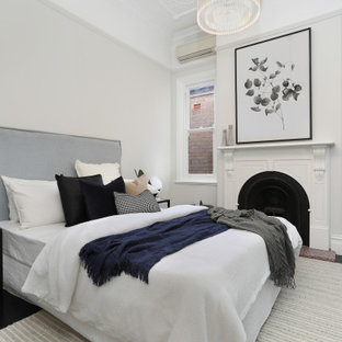 Contemporary bedroom in Sydney with white walls, painted wood floors, a standard fireplace and black floor.