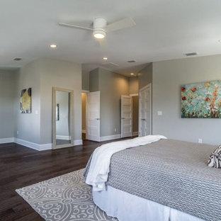 Ejemplo de dormitorio principal, tradicional renovado, grande, con paredes grises, suelo de madera oscura, chimeneas suspendidas y suelo marrón