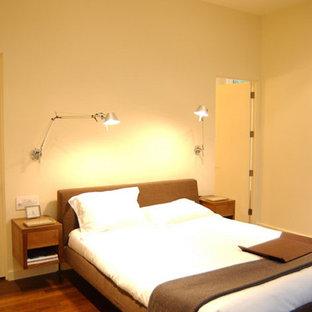 Ejemplo de dormitorio minimalista con suelo de madera en tonos medios
