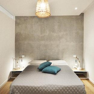 Ispirazione per una camera da letto design di medie dimensioni con pareti grigie e pavimento in legno massello medio