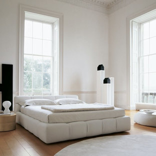 Inspiration for a large modern master light wood floor and beige floor bedroom remodel in Calgary with white walls and no fireplace