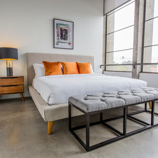 Small midcentury loft-style bedroom in San Diego with grey walls, concrete floors and no fireplace.