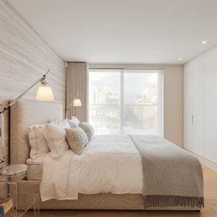 Esempio di una camera degli ospiti contemporanea di medie dimensioni con pareti beige, parquet chiaro e nessun camino