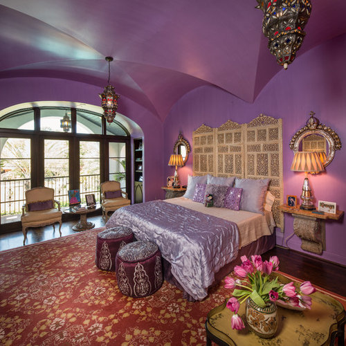Example of a large tuscan master dark wood floor bedroom design in Houston  with purple walls