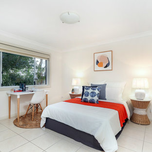 Inspiration for a beach style guest bedroom in Sydney with beige walls and beige floor.