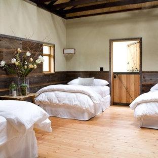 Стильный дизайн: большая гостевая спальня в стиле кантри с бежевыми стенами, светлым паркетным полом и оранжевым полом без камина - последний тренд