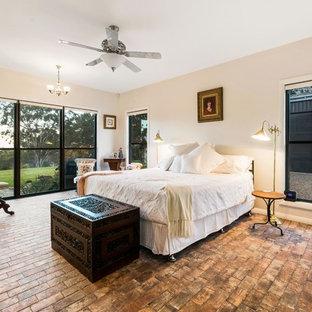 Diseño de dormitorio principal, de estilo de casa de campo, con paredes beige, suelo de ladrillo y suelo marrón