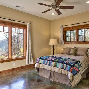 This is an example of a mid-sized traditional master bedroom in Other with beige walls, concrete floors and brown floor.