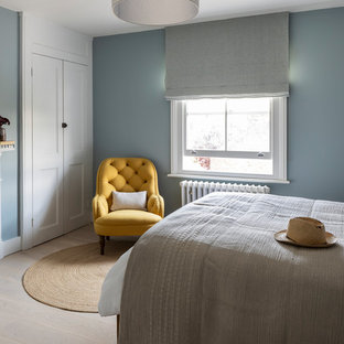 Photo of a mid-sized transitional guest bedroom in London with blue walls, light hardwood floors, a standard fireplace, a plaster fireplace surround and beige floor.
