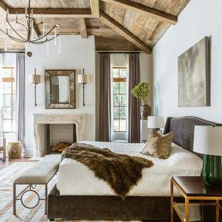 Modelo de dormitorio principal, de estilo de casa de campo, grande, con paredes blancas, suelo de madera clara, chimenea tradicional, marco de chimenea de baldosas y/o azulejos y suelo beige