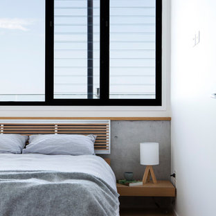 Inspiration for a contemporary bedroom in Sunshine Coast with white walls, light hardwood floors and beige floor.