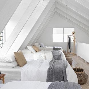 Immagine di una camera da letto stile loft costiera con pareti bianche, parquet chiaro, pavimento beige, travi a vista e soffitto a volta