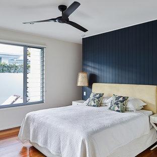 Inspiration for a beach style master bedroom in Gold Coast - Tweed with beige walls, dark hardwood floors and brown floor.