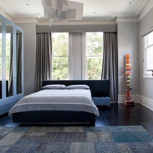 ヴィクトリアン調のおしゃれな客用寝室 (グレーの壁、濃色無垢フローリング、標準型暖炉、木材の暖炉まわり、茶色い床) のインテリア