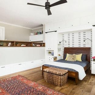 Ejemplo de dormitorio principal, campestre, extra grande, sin chimenea, con paredes beige, suelo de madera en tonos medios, marco de chimenea de ladrillo y suelo marrón