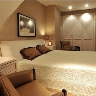 Foto de dormitorio principal, moderno, pequeño, con paredes beige, suelo de madera clara y suelo marrón