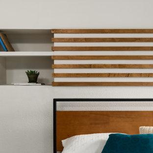 Ejemplo de dormitorio tipo loft, moderno, de tamaño medio, con paredes blancas, suelo de baldosas de porcelana, chimenea tradicional, marco de chimenea de ladrillo y suelo gris