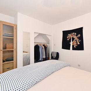 Imagen de dormitorio principal, rústico, de tamaño medio, sin chimenea, con paredes blancas, suelo de madera clara, marco de chimenea de yeso y suelo marrón