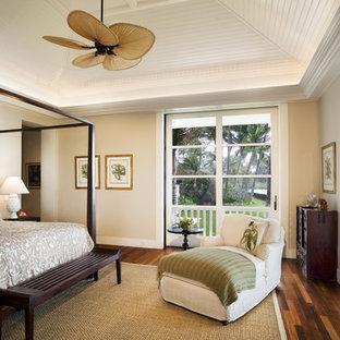 Modelo de dormitorio tropical con paredes beige y suelo de madera oscura