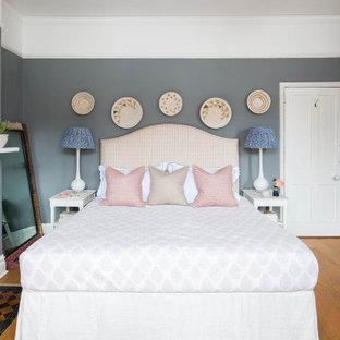 Неиссякаемый источник вдохновения для домашнего уюта: хозяйская спальня в викторианском стиле с серыми стенами, светлым паркетным полом, печью-буржуйкой и фасадом камина из плитки