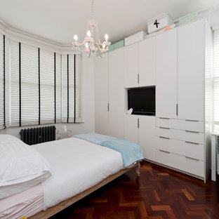 Small eclectic master dark wood floor and red floor bedroom photo in Other with white walls