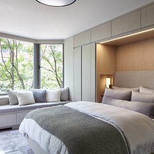 Modelo de dormitorio principal, minimalista, pequeño, con paredes grises, suelo de madera en tonos medios y suelo gris
