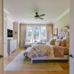 Large arts and crafts master medium tone wood floor bedroom photo in Portland with beige walls and no fireplace