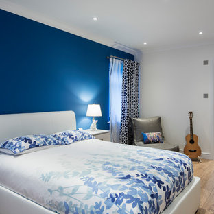 Medium sized contemporary bedroom in West Midlands with laminate floors, beige floors, blue walls and no fireplace.