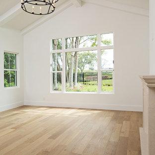 Modelo de dormitorio principal, extra grande, con paredes blancas, suelo de madera clara, chimenea tradicional, marco de chimenea de hormigón y suelo marrón