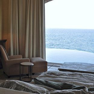 На фото: большая хозяйская спальня в средиземноморском стиле с бежевыми стенами, полом из травертина и бежевым полом без камина с