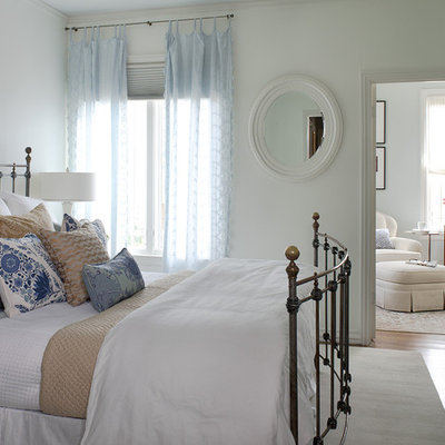 Elegant medium tone wood floor bedroom photo in San Francisco with white walls and no fireplace