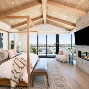 Ejemplo de dormitorio principal, abovedado y madera, clásico renovado, grande, con paredes beige, suelo de madera clara, chimenea lineal, marco de chimenea de piedra y suelo marrón