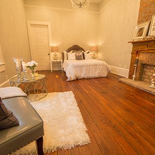 Foto de dormitorio principal, clásico, grande, con paredes beige, suelo de madera oscura, chimenea tradicional y marco de chimenea de ladrillo