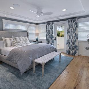 На фото: с высоким бюджетом хозяйские спальни среднего размера в морском стиле с синими стенами, светлым паркетным полом, стандартным камином и фасадом камина из плитки