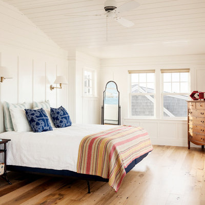 Example of a beach style medium tone wood floor bedroom design in Boston with white walls and no fireplace